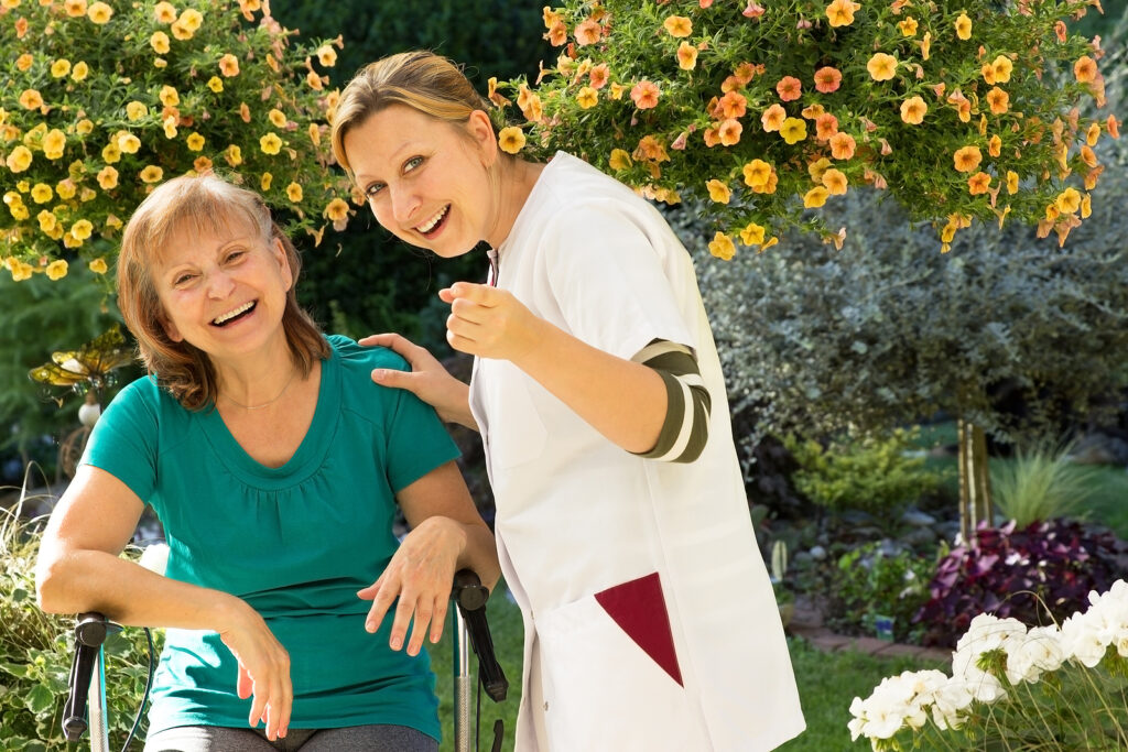 Senior and her nurse standing in the garden and pointing at camera